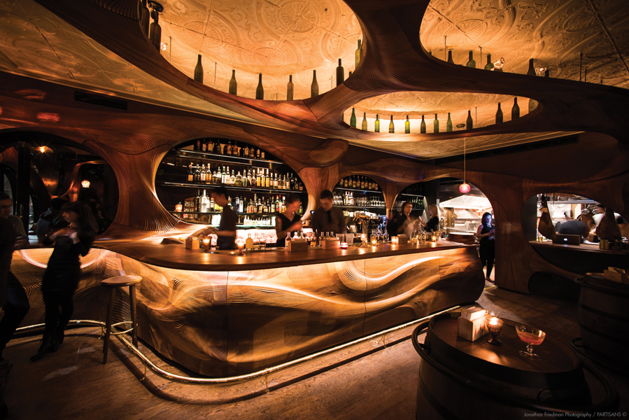 The seductive interior of Bar Raval is partially achieved through the organic curves of the CNC-milled mahogany bar.