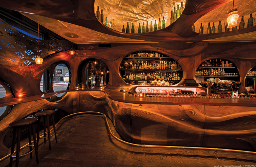 The counter, walls and ceiling of Bar Raval are adorned with CNC-cut solid mahogony boards. Instead of straight seams between the panels, the designers created S-shaped joints that accentuate the bar's curvilinear geometries and accommodate for seasonal warping and shrinkage of the wood. Integrated lighting, shelving and display areas are also meticulously executed in this compact design.