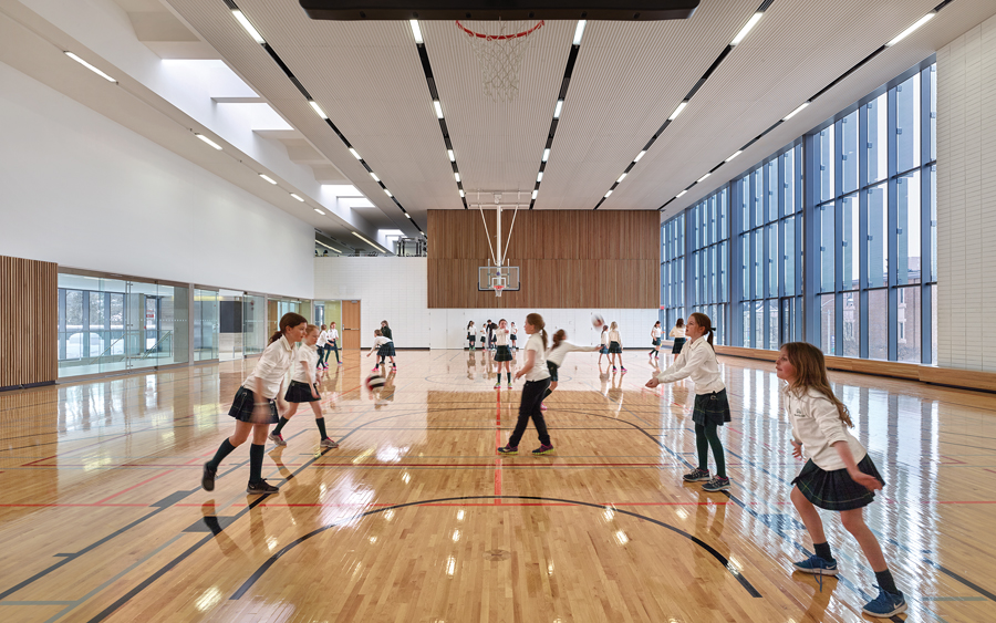 Tall enough for competitive volleyball tournaments, the gymnasium includes ample glazing and skylights.