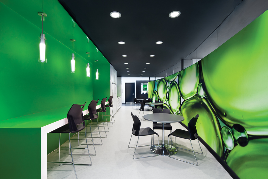 A green mural inspired by cellular forms envelops a waiting room, which doubles as an employee break area.