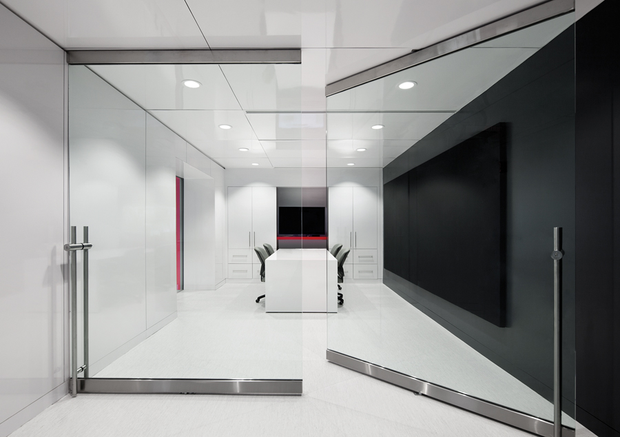 Oversized glass doors pivot open to the centre's main conference room.