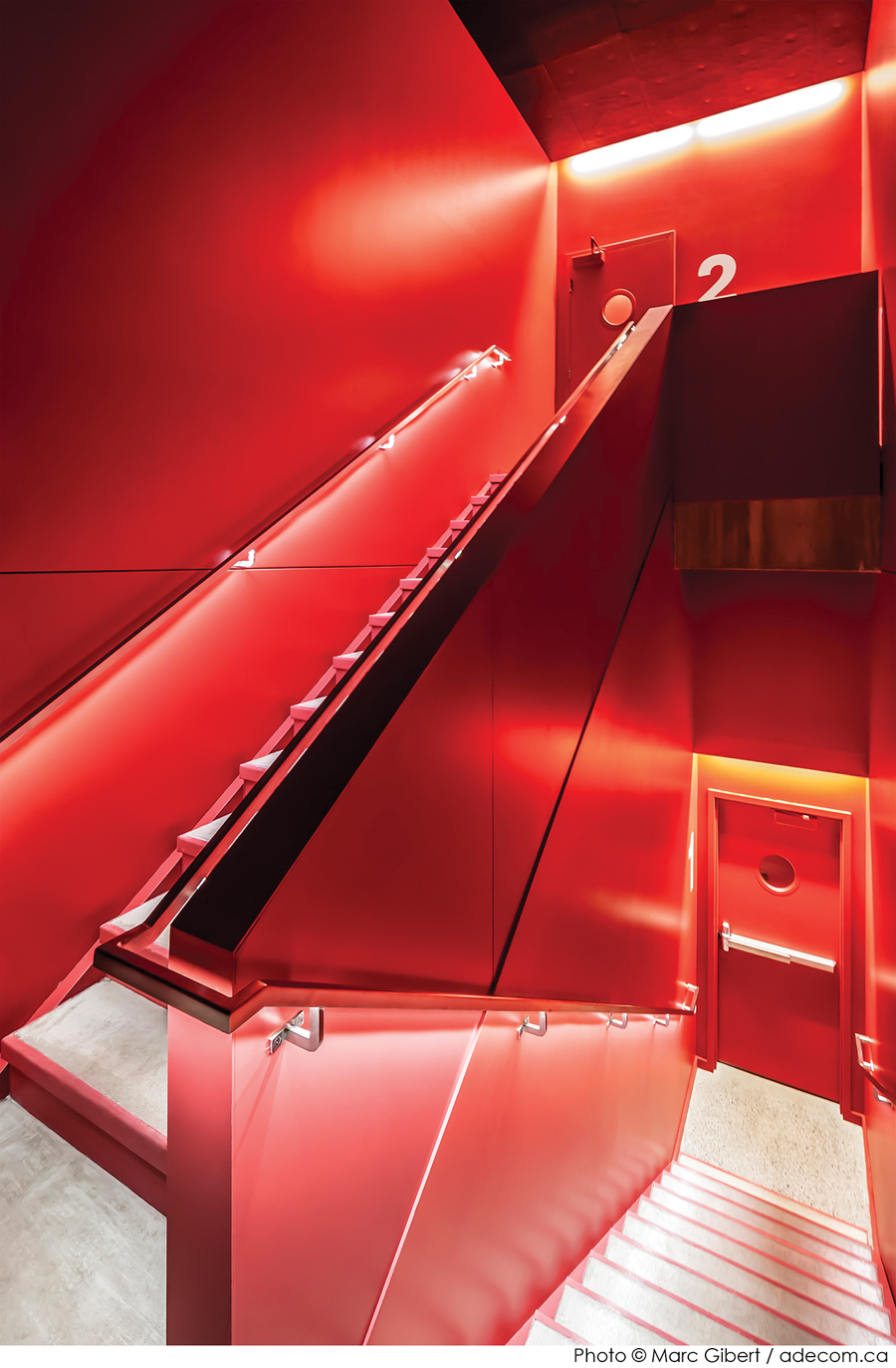 A bright red stairway maintains the project's minimalist colour palette.