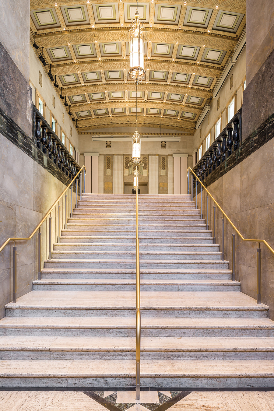 View of the grand stair leading to the banking hall. The rehabilitated coffered ceilings conceal acoustic controls, fire sprinklers, and return air vents.