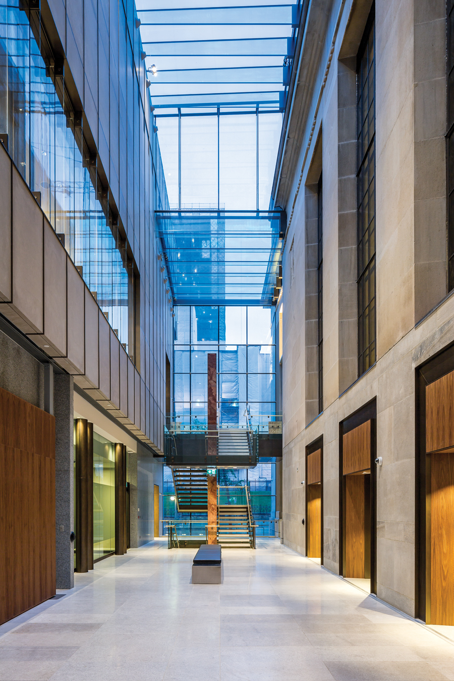 The fully glazed atrium connects the historic banking hall to a contemporary addition. Conceived as a second stone box, the addition includes a granite base topped by limestone above, set out in a modular pattern with bronze inlaid joints.