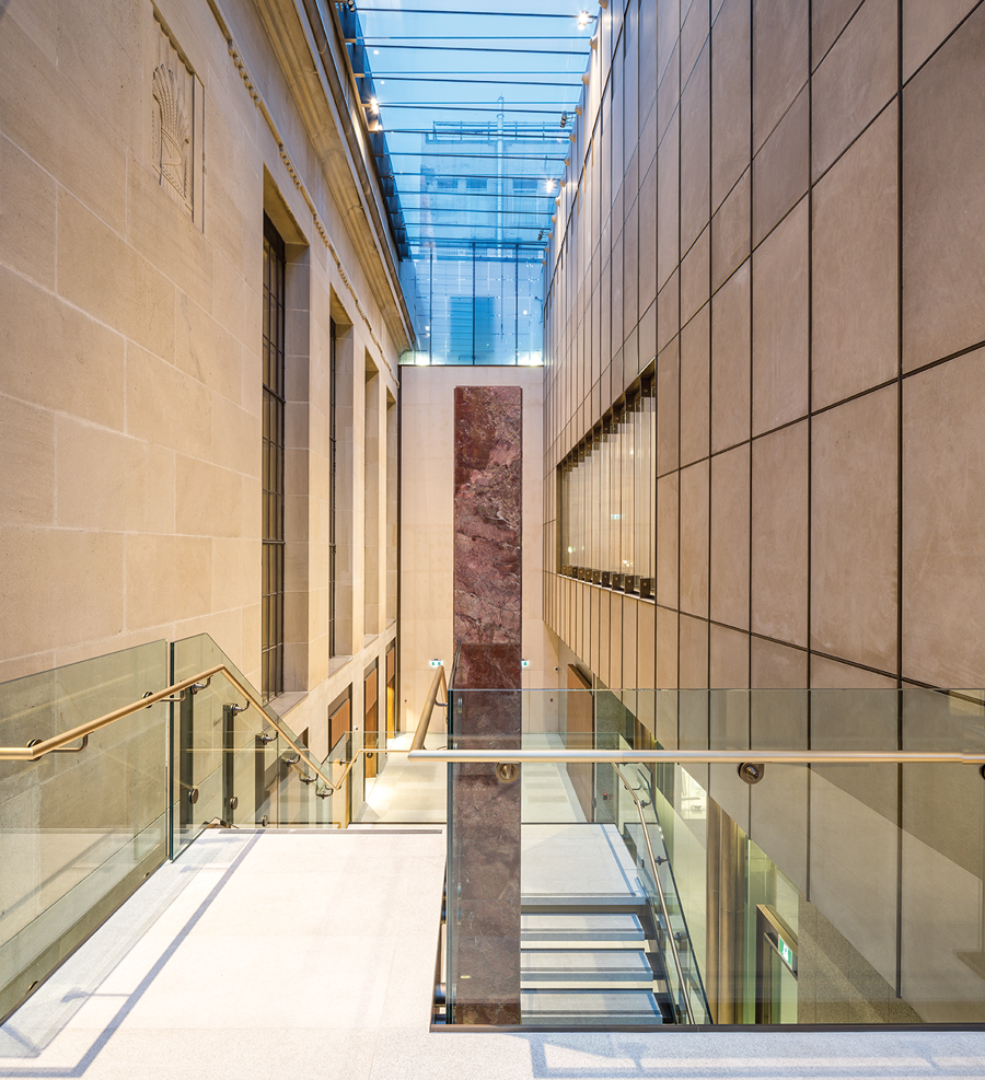 A stair in the new atrium wraps around a richly veined deep red slab of Cape Breton marble.