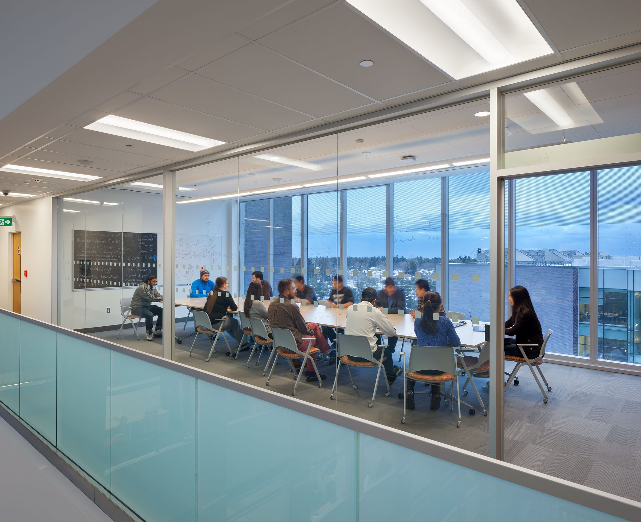 Collaborative spaces at the ends of the floorplates enjoy writable glass walls and views of the city in the distance. Photo by Tom Arban.