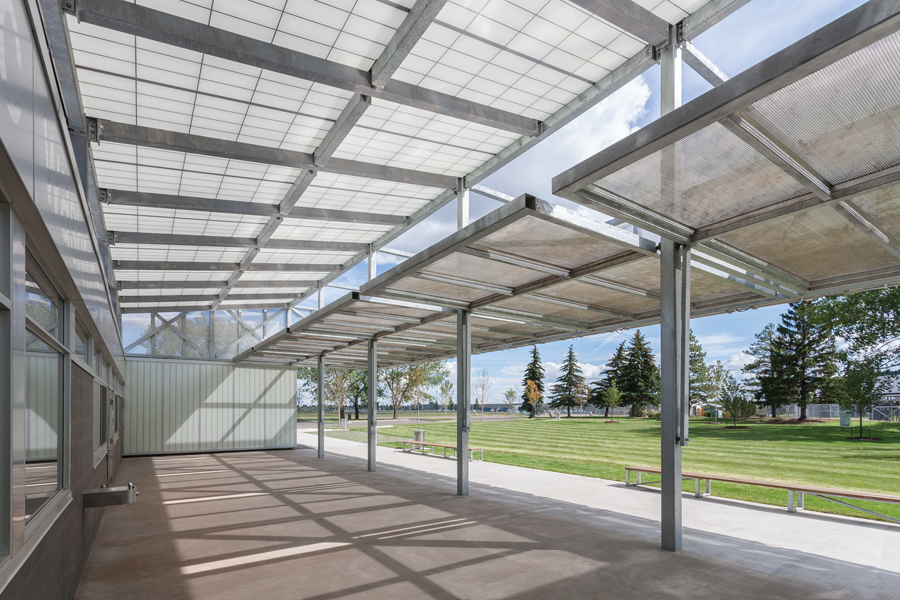 On the long side  of the pavilion, full-height panels flip up to create a canopy entrance to a public courtyard with a concession and public washrooms. Photo: Bruce Edward / Yellow Camera