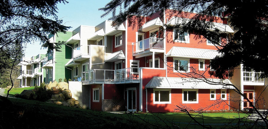Bordering a river, the Pacific Gardens Cohousing development in Nanaimo includes a mix of two and three-storey volumes to accommodate the sloping site.