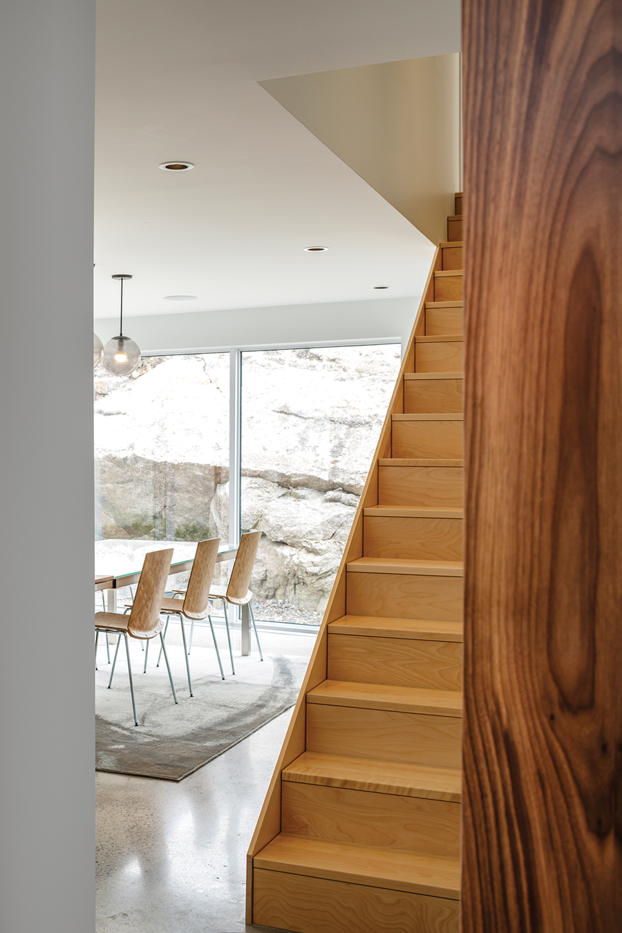 An exposed rock face forms a dramatic backdrop for the dining area.