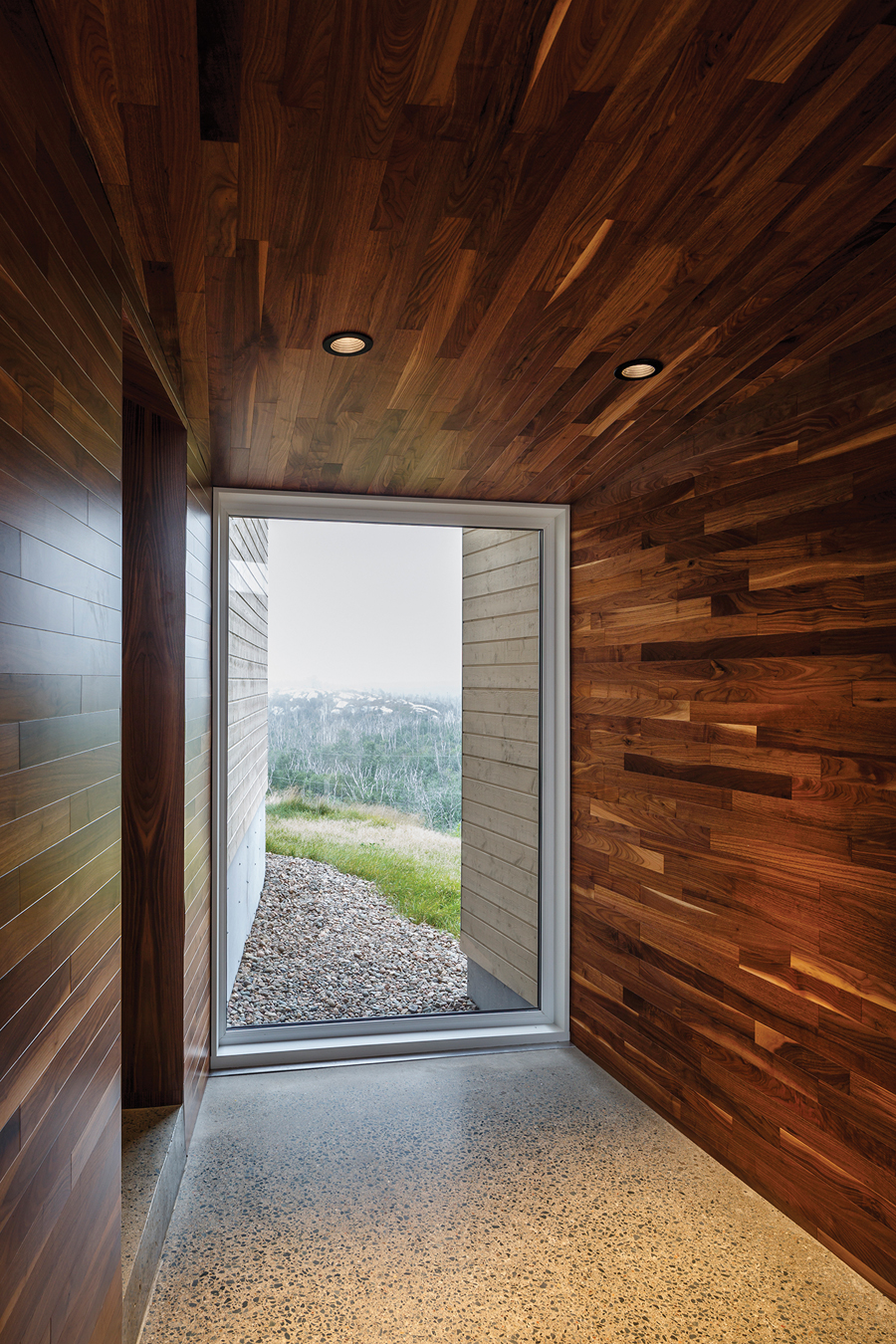 The entrance foyer is capped by a floor-to-ceiling window that gives a glimpse of the landscape views visible from the house's living spaces.