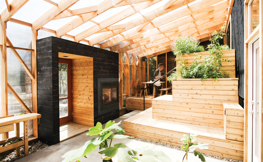 A structural wood lattice wraps a solarium addition to a Calgary home. Designed to provide year-round warmth, the space includes a built-in fireplace, tiered seating and low-maintenance plants.