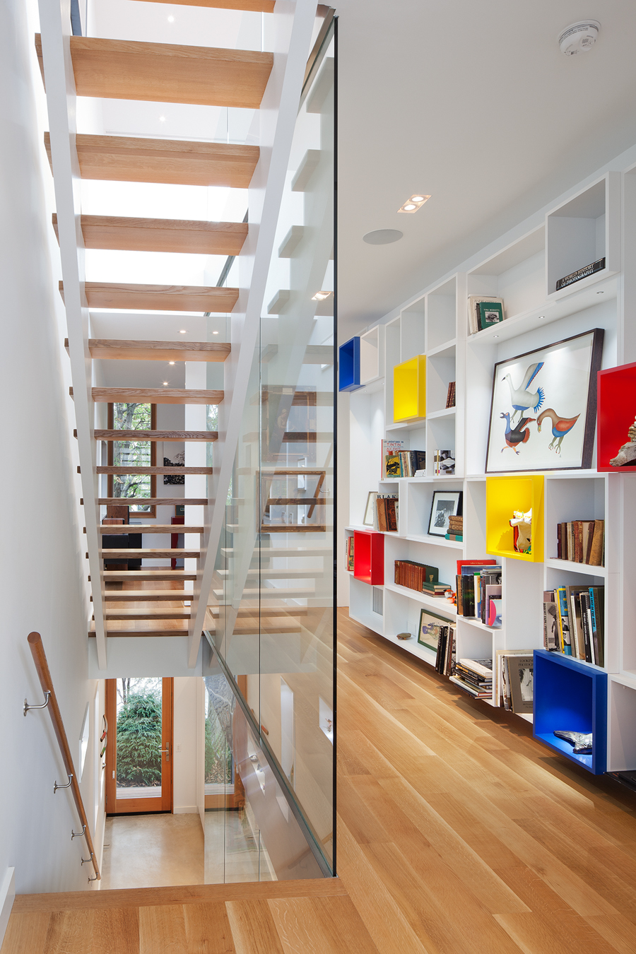 A custom, modular bookcase system enlivens the second floor of House 2.