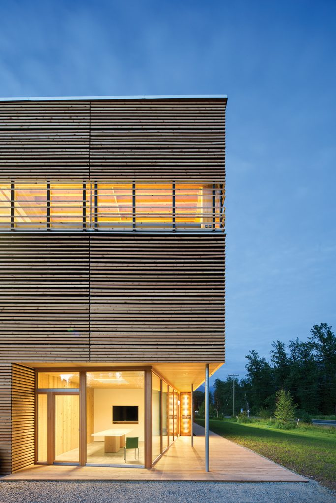A wood slat screen provides differing degrees of solar shading on the various façades.