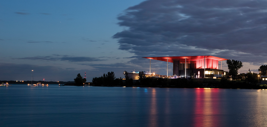 View of the amphitheatre reflected in the St. Lawrence River at night. Photo by Adrien Williams.