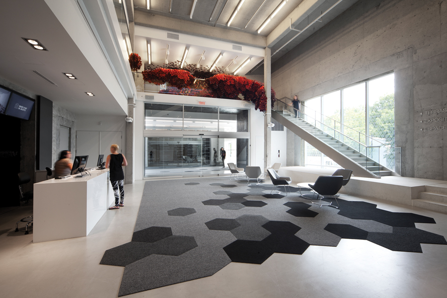 A concrete floor was removed to enlarge the existing lobby into a spacious two-storey space, flanked by staircases to the upper-floor exhibition and reception areas.