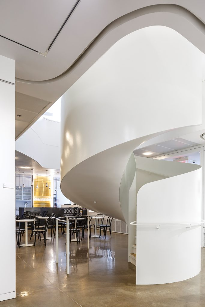 The spiral stair at the edge of the café ascends to the main reading areas on the second floor.
