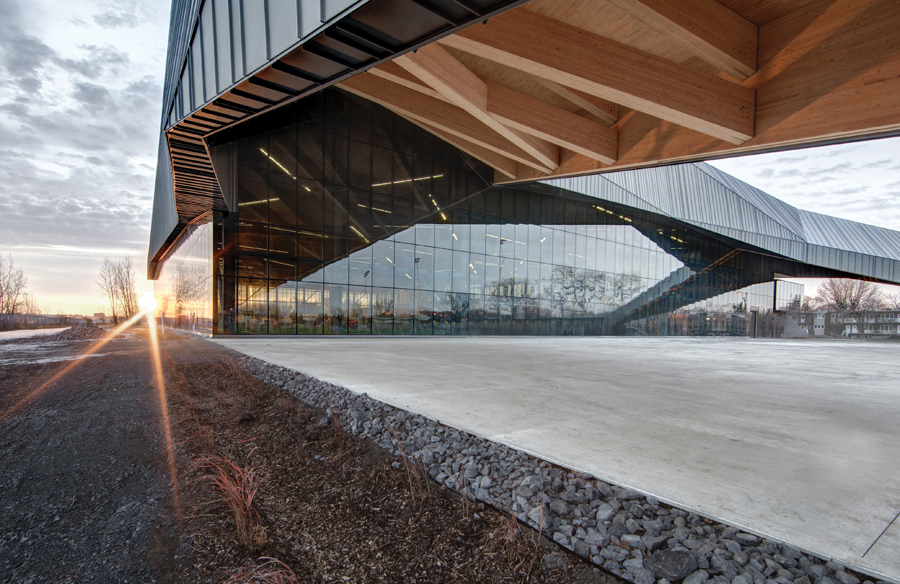A zinc-clad roof with a wooden underside hovers over an indoor soccer field northeast of downtown Montreal. The structure stretches out beyond the field to frame a public plaza and outdoor field.