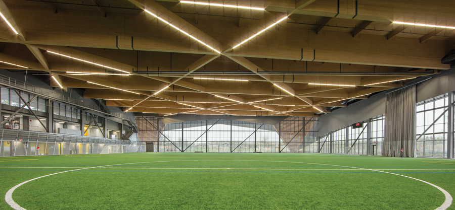 Mass timber members set at dynamic angles span the indoor pitch, creating a dramatic roof for soccer games.