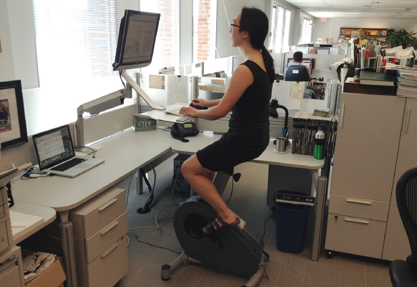 Editor Elsa Lam exercises at work with a LifeSpan Bike Desk paired with a Humanscale QuickStand 