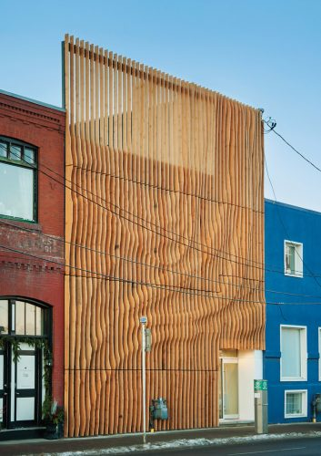 Junction 9 yoga studio was given a fresh look with a shapely screen of vertical fins, made of 100-year-old fir reclaimed from an abandoned Alberta granary. Photo by MHB PHOTO GRAF