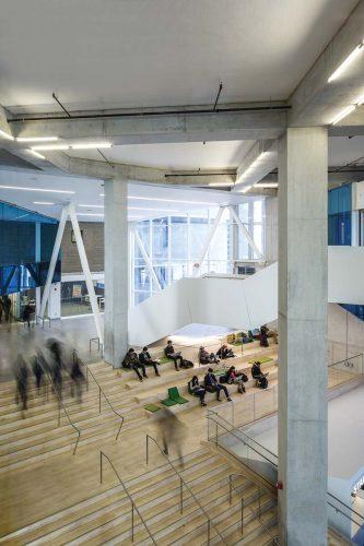 The spacious lobby acts as a communal foyer for students from different departments. | Le hall spa-cieux agit comme un foyer commu-nal pour les étudiants des différents départements.