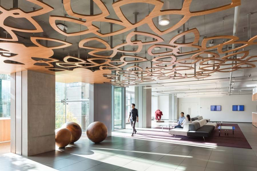 A petal motif, abstracted from the TELUS logo, creates a leafy ceiling for an office lobby designed by omb. The firm curated a comprehensive, customized art program to ensure the integration of art, interior design and client vision within the TELUS office spaces. Photo by Ema Peter
