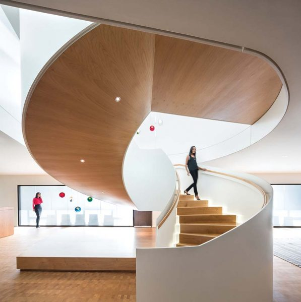 An elegant spiral stair connects two floors of the TELUS offices as part of the interior fit-out designed by omb. Glass lights by Canadian designer Omer Arbel add sparkle to the space. Photo by Ema Peter