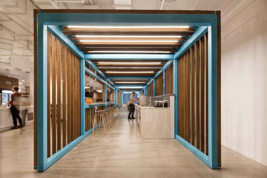 A vibrant blue metal-and-wood scaffold frames an espresso bar and meeting room in Shopify's Montreal office, lending structure to the open-concept workspace. Photo by Claude-Simon Langlois