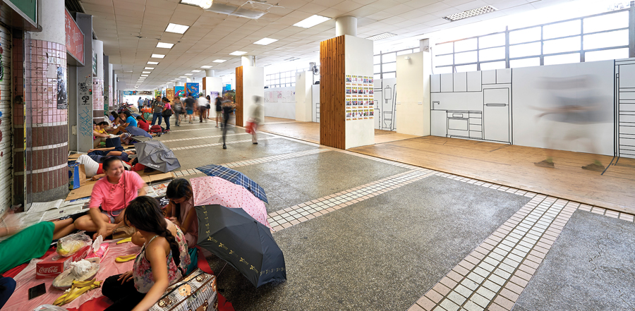 Migrant domestic workers socialize in Hong Kong's former Central Market, opposite an exhibition that includes 1:1 drawings of the tiny spaces in their employers' apartments that they live in during most of the week. Photo by Eddie C.Y. Lam