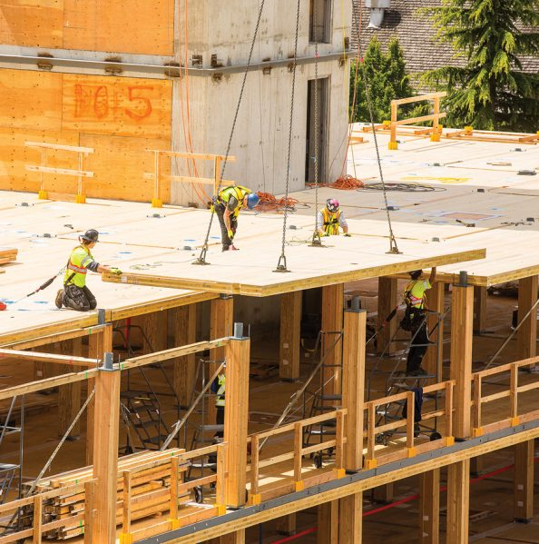 A CLT floor slab is lowered into place and fastened to the glulam columns. Photo: KK Law, Courtesy of Naturally: Wood.