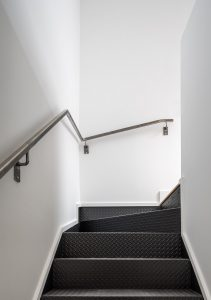 Checker-patterned steel stairs are used throughout, making use of economical industrially produced materials.