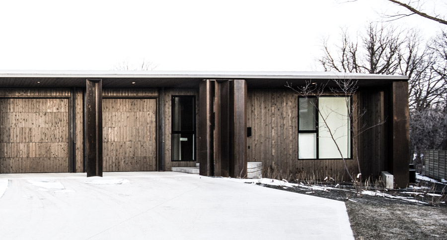 Appearing as a modest bungalow, the house takes advantage of its geometry to accommodate a three-car garage on one side, and expansive views on the opposite side.